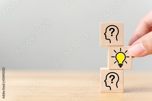 Obraz Concept creative idea and innovation. Hand picked wooden cube block with head human symbol and light bulb icon - fototapety do salonu