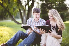 White Christian Couple Enjoying Reading The Bible In The Middle Of A Field
