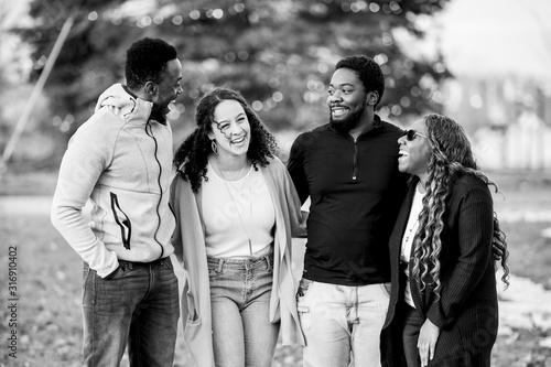 Fototapeta Cute greyscale shot of friends joking and laughing together