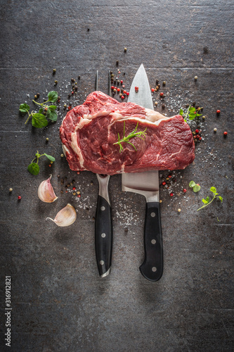 Fototapeta Raw beef steak with fork and knife salt pepper and herbs on dark concrete background obraz