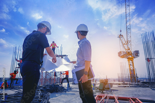 Obraz Structural engineer and architect working with blueprints discuss at the outdoors construction site. - fototapety do salonu