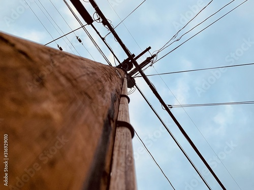 Low angle view of looking up a wooden power line pole