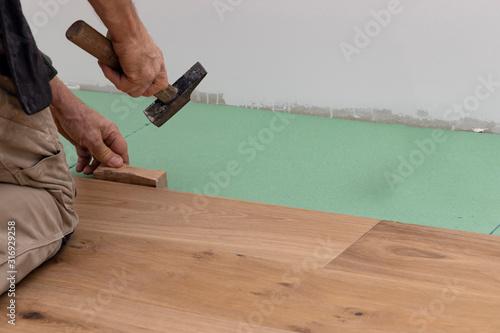 Fotografija Man lays parquet floorand beats the floorboards with the hammer.