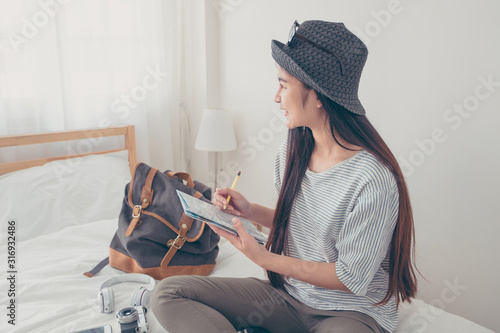 Fotografia Young asian woman traveller planning vacation holiday expedition on bed