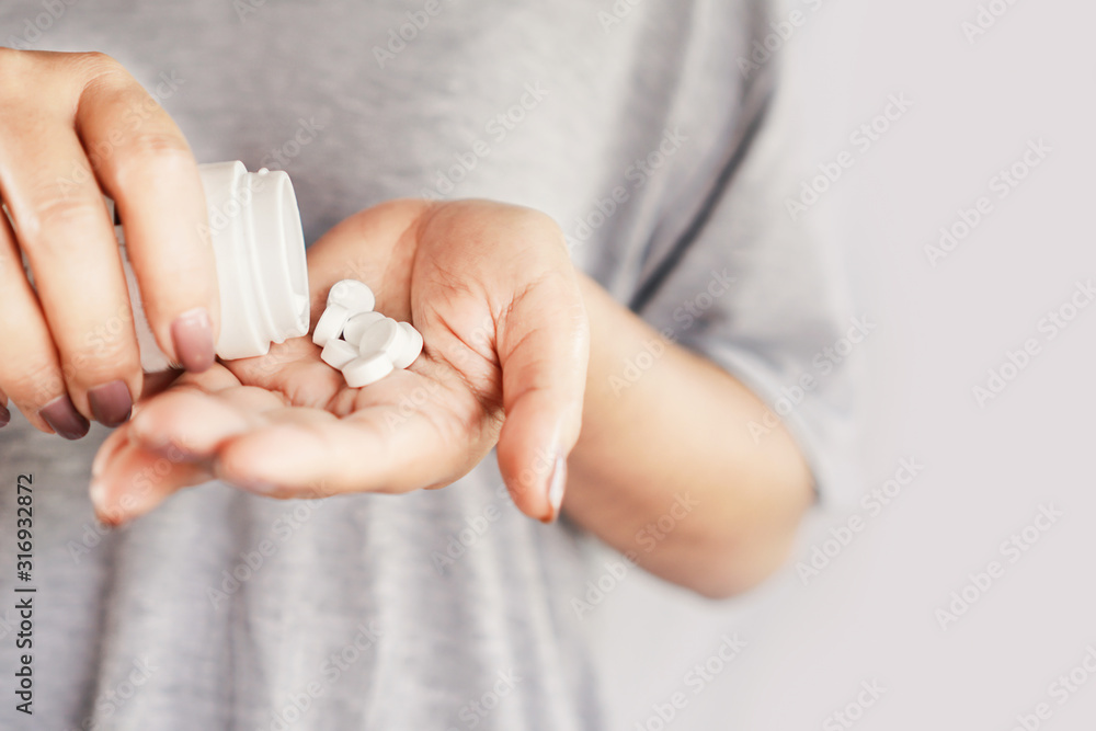 Fototapeta closeup woman hand holding medicine bottle taking overdose pills