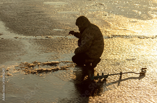 Obraz A fisherman catches fish on ice at dawn - fototapety do salonu
