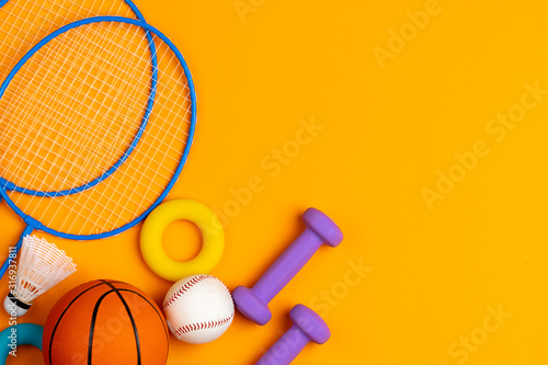 Fotografia Assortment of sport equipment on yellow background, top view