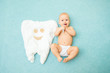 canvas print picture - Cute baby lies with a toothbrush on a blue background. White tooth made of fabric. Medicine, dentistry, health concept