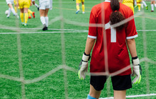 Unrecognizable Female Soccer Players Playing A Game On The Soccer Field.