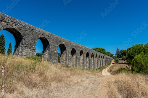Photo Roman aqueduct of Pegoes surrounded by greenery under sunlight in Tomar in Portu