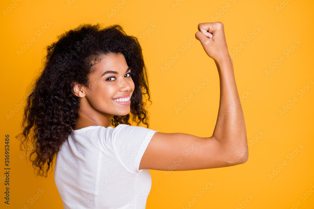 Fototapeta Close-up profile side view portrait of her she nice attractive lovely brunet cheerful wavy-haired girl showing strong muscles isolated over bright vivid shine vibrant yellow color background