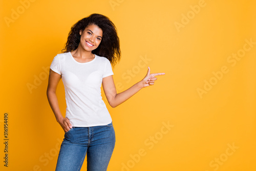Photo of wavy cheerful girlfriend wearing white t-shirt pointing at empty space in jeans denim isolated vibrant yellow color background
