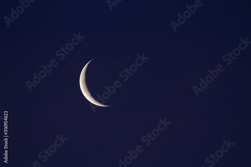 Leinwand Poster Waning crescent moon in dark blue sky
