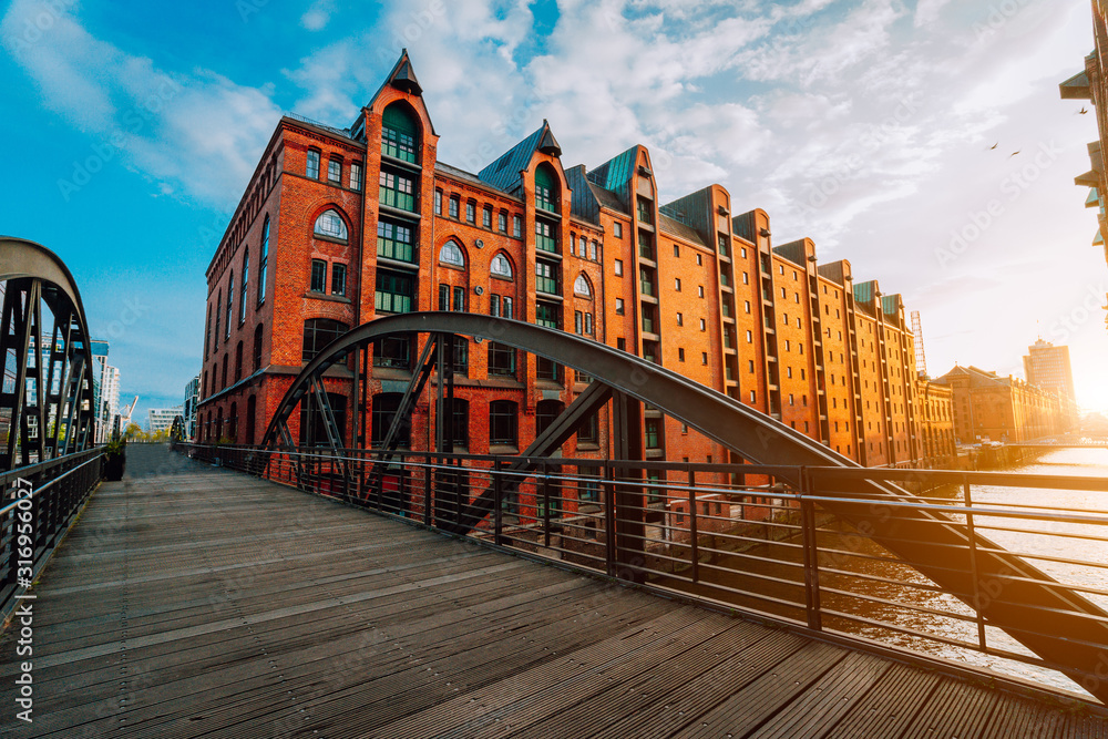 Fototapeta Arch bridge over canals in the Speicherstadt of Hamburg. Warm evening sun light on red brick building
