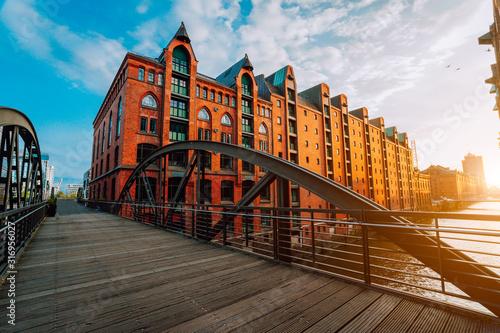 Fototapeta Arch bridge over canals in the Speicherstadt of Hamburg. Warm evening sun light on red brick building obraz