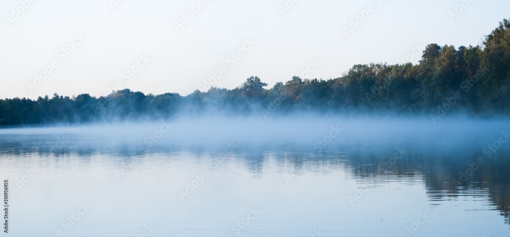 Fototapeta Wide shot of a beautiful lake with a light fog forming above it