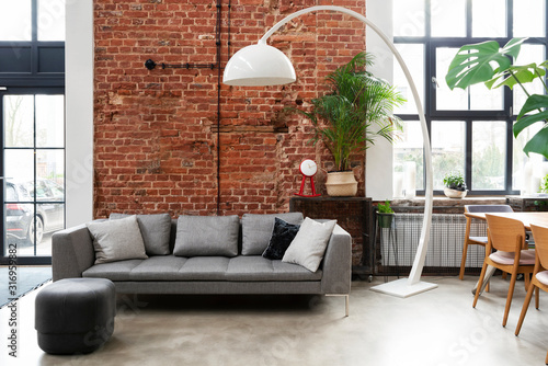 Photo Living room interior in loft apartment in industrial style with brick wall, grey stylish sofa and big window