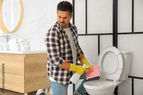 Obraz na plátne Young man feeling disgust while cleaning toilet bowl in bathroom