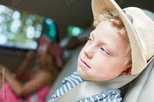 Junge sitzt müde auf der Rückbank im Auto #316961426