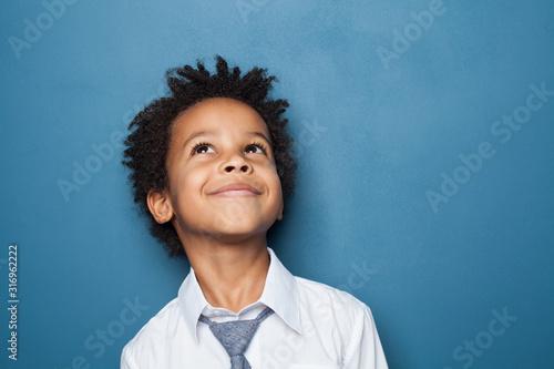 Happy kid school boy portrait. Little child boy looking up on blue background