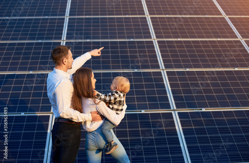 Obraz Husband shows his family the solar panels on the background. Blond child in arms of wife. Young family keeps up with the times choosing solar heating - fototapety do salonu
