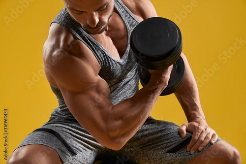 Fotografia, Obraz Muscular young gentleman pumping up biceps