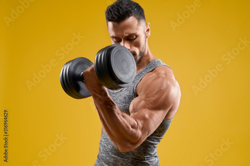 Cuadros en Lienzo Handsome bodybuilder working out with dumbbell