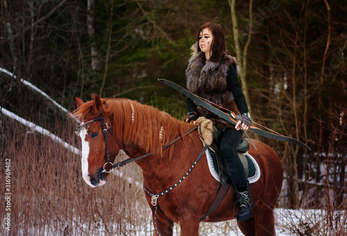 Photo a Viking girl riding a red horse painted in black runes