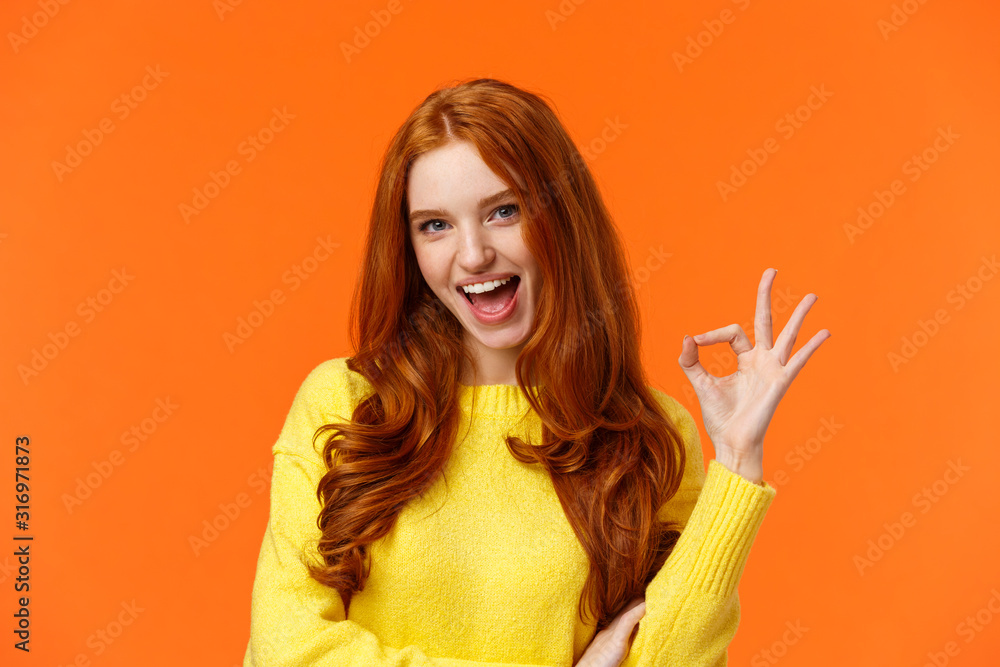 Fototapeta Sassy and daring cool redhead girl with curls, showing okay excellent gesture and smiling excited, assure party be awesome, give permission, say yes, confirm or recommend something, orange background