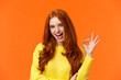 canvas print picture - Sassy and daring cool redhead girl with curls, showing okay excellent gesture and smiling excited, assure party be awesome, give permission, say yes, confirm or recommend something, orange background