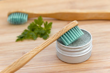 Bamboo Toothbrushes And Solid Toothpaste In Metal Tin On Wood Background. Zero Waste, Plastic Free, Environment Concept