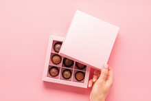 Female Hand Opens A Box With Sweets Pink Background . Gifts Festive Food Love Concept. Horizontal Frame
