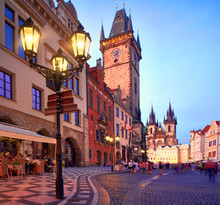 Prague, Old City Hall On The Town Square Early Evening, Historic Architecture Of Houses And Church Of St. Mary Before Tyn Illuminated With Setting Sun And Street Lights. Beautiful Prague On Sunset.