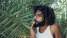 Black Man With Dreadlocks Smoking Weed Joint On Background Of Palm Leafs