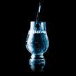 Leinwanddruck Bild - Liquid poured into a glas - blue toned isolated on black