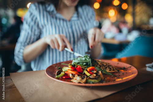 Fototapeta close up of woman in restaurant eating obraz