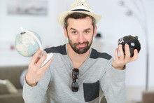 Man Holding Globe And Piggy Ba...