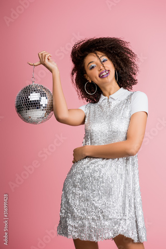 cheerful african american girl in paillettes dress holding disco ball, isolated on pink - 316991428