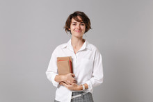 Smiling Beautiful Young Business Woman In White Shirt Posing Isolated On Grey Wall Background Studio Portrait. Achievement Career Wealth Business Concept. Mock Up Copy Space. Holding Books, Notebooks.