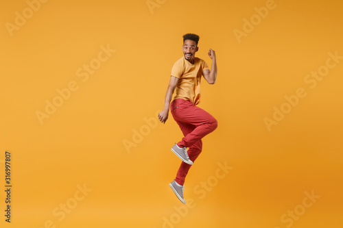 Fototapeta Excited funny young african american guy in casual clothes posing isolated on yellow orange wall background studio portrait. People lifestyle concept. Mock up copy space. Jumping doing winner gesture. obraz