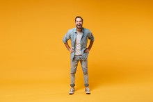 Laughing Young Bearded Man In Casual Blue Shirt Posing Isolated On Yellow Orange Background, Studio Portrait. People Emotions Lifestyle Concept. Mock Up Copy Space. Standing With Arms Akimbo On Waist.