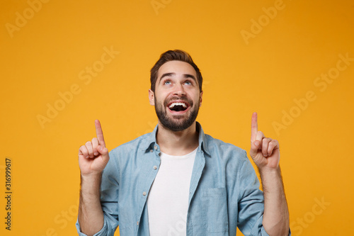 Fotografía Cheerful young bearded man in casual blue shirt posing isolated on yellow orange background studio portrait