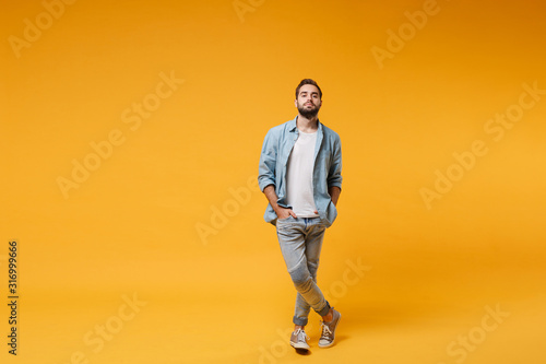 Obraz Handsome young bearded man in casual blue shirt posing isolated on yellow orange background, studio portrait. People sincere emotions lifestyle concept. Mock up copy space. Holding hands in pockets. - fototapety do salonu