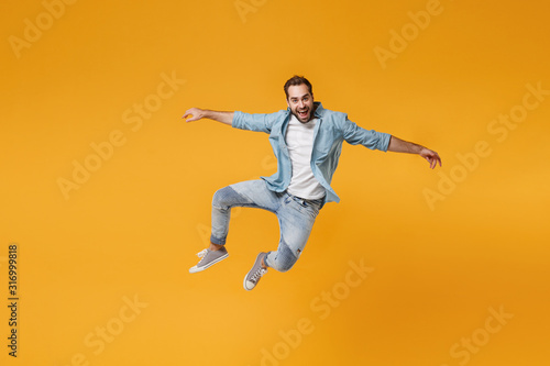 Cheerful young bearded man in casual blue shirt posing isolated on yellow orange background, studio portrait. People sincere emotions lifestyle concept. Mock up copy space. Jumping spreading hands. - 316999818