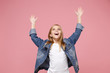 canvas print picture - Cheerful little blonde kid girl 12-13 years old in denim jacket isolated on pastel pink background children studio portrait. Childhood lifestyle concept. Mock up copy space. Spreading rising hands up.