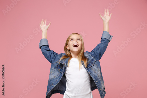 Cheerful little blonde kid girl 12-13 years old in denim jacket isolated on pastel pink background children studio portrait. Childhood lifestyle concept. Mock up copy space. Spreading rising hands up.