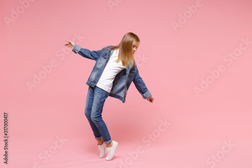 Fotografie, Tablou Little blonde kid girl 12-13 years old in denim jacket isolated on pastel pink wall background children studio portrait