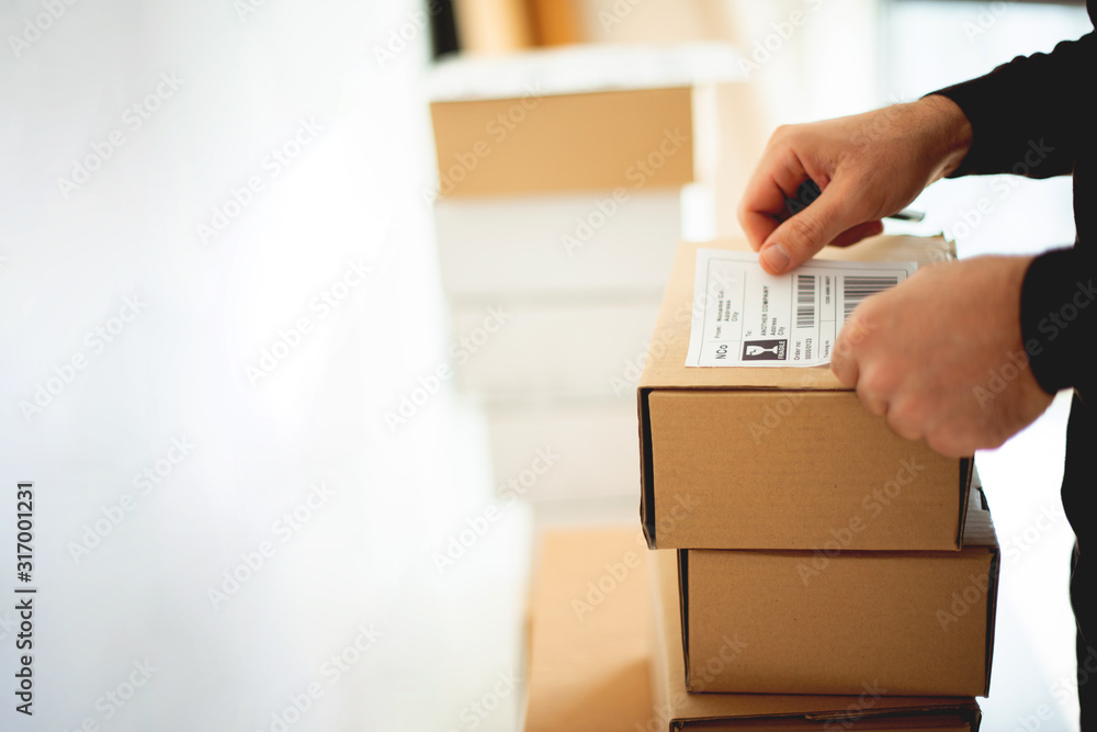 Fototapeta Delivery service, applying a shipping label