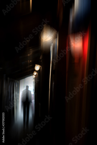 Silhouette of a man in a coat in a dark alley on a rainy night Wallpaper Mural