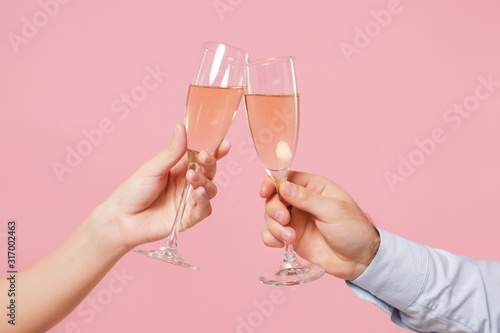 Fotografía Close up cropped photo of female, male hold in hands glass of champagne isolated on pastel pink background